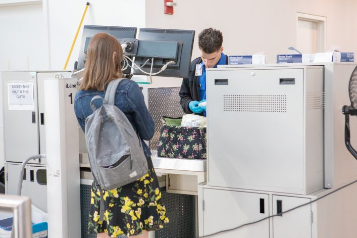 Female airline passenger  having bag searched by TSA
