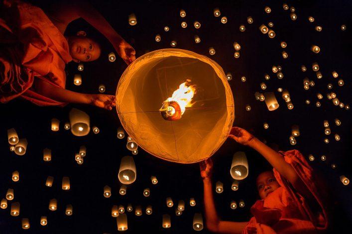 Novice-monk-lights-floating-lanterns-made-of-paper-in-Loi-Krathong-or-Loy-Krathong-day.-shutterstock_453720424