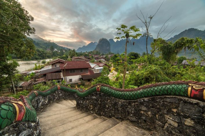 Traditional-lao-village-with-temple-stairs-and-mountain-background-near-Vang-Vieng-Laos.-shutterstock_688550302