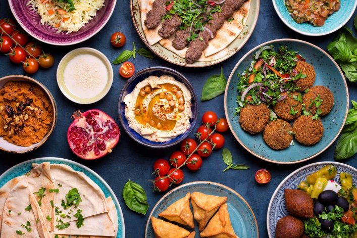 Middle-eastern-or-arabic-dishes-and-assorted-meze-concrete-rustic-background.-Meat-kebab-falafel-baba-ghanoush-muhammara-hummus-sambusak-rice-tahini-kibbeh-pita.-Halshutterstock_563091901