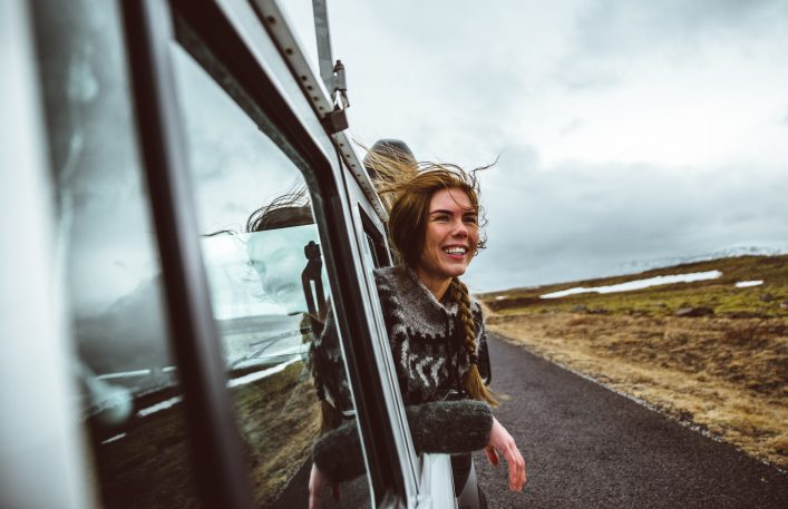Beautiful icelandic girl enjoying the landscape in Iceland ,looking out the car window