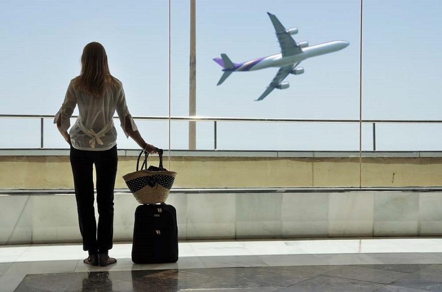 Frau steht in der Abflughalle eines Flughafens