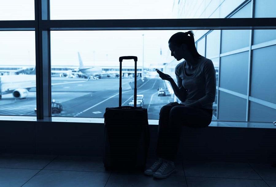 Frau sitzt am Flughafen und wartet auf ihren verspäteten Flug