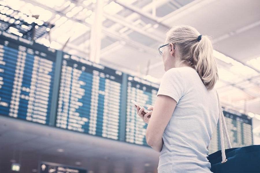Frau steht am Flughafen und betrachtet die Abflugzeiten