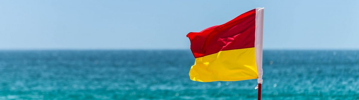 Red And Yellow Warning Sign Flag at the Beach