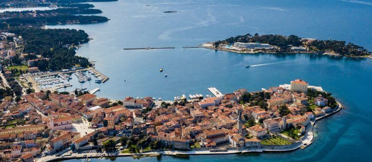Aerial-shot-of-the-Croatian-town-of-Porec.-The-town-of-Porec-is-almost-2000-years-old-and-is-set-around-a-harbour-protected-from-the-sea-by-the-small-island-of-Sveti-Nikola.-shutterstock_1046025004