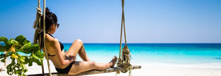 Girl in black bikini relaxing on beach swing