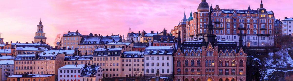 Sodermalm-island-in-Stockholm-Sweden.-Beautiful-orange-violet-and-pink-sky-at-sunrise-is-reflected.-shutterstock_1296212287