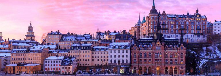 Sodermalm-island-in-Stockholm-Sweden.-Beautiful-orange-violet-and-pink-sky-at-sunrise-is-reflected.-shutterstock_1296212287