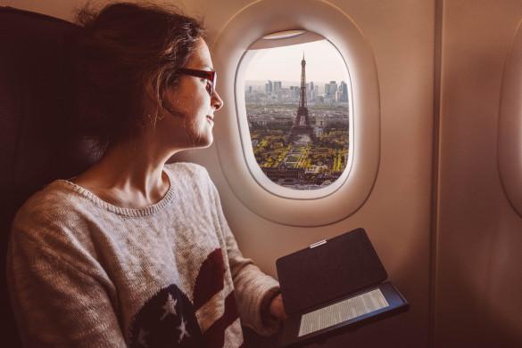 Smiling woman enjoying Paris from the airplane window