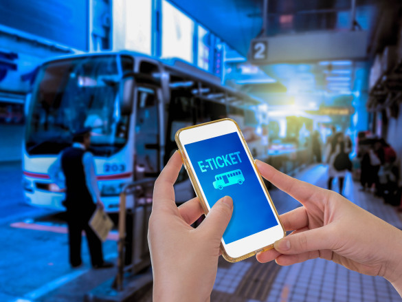 hand-holding-mobile-phone-with-e-ticket-word-with-blur-bus-terminal-background-shutterstock_360686624-2-585x439