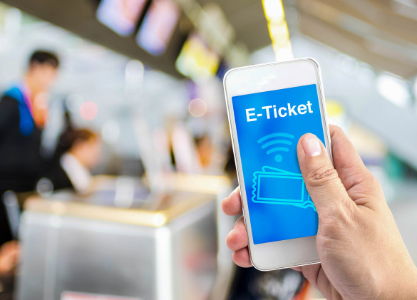 hand-holding-mobile-with-e-ticket-with-blur-airport-check-in-background-shutterstock_300059927-2-585x421