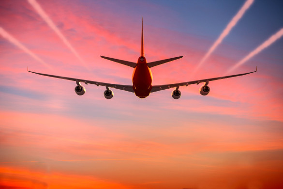 airplane-flying-in-the-sky-at-sunset-with-vapor-trails-istock_50476228_xlarge-2-585x390